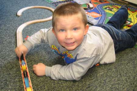 Billy and other children in the morning program play while developing fine and gross motor skills.